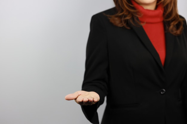 Femme d'affaires portant l'uniforme de costume noir et rouge avec confiance tout en montrant quelque chose sur sa main