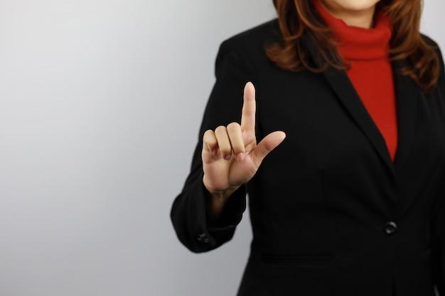 Femme d'affaires portant l'uniforme de costume noir et rouge avec confiance tout en pointant quelque chose
