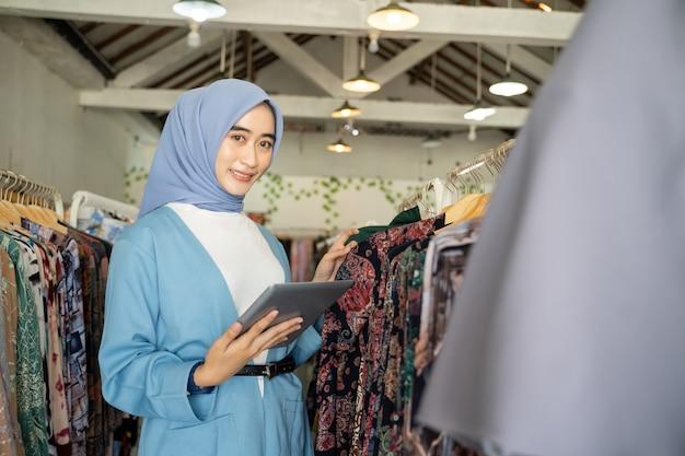 Une femme d'affaires portant un voile bleu sourit lors de l'utilisation d'une tablette tout en tenant des vêtements