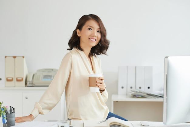 Femme d'affaires posant avec un café
