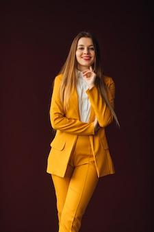 Femme d'affaires posant dans un élégant costume jaune contre l'espace du mur. sourire.