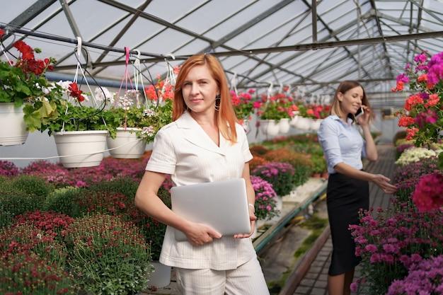 Femme d'affaires posant avec un ordinateur portable pendant que son partenaire discutait au téléphone d'une proposition dans une maison verte avec des fleurs.