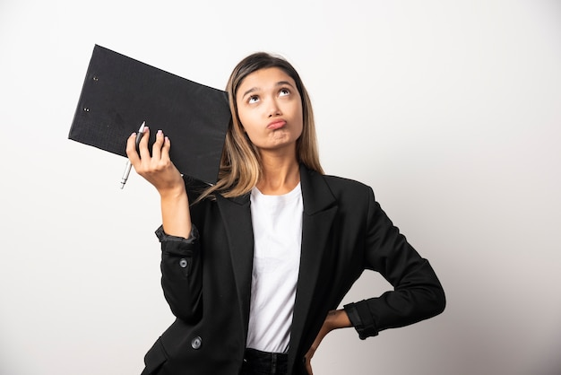 Femme d'affaires posant et tenant le presse-papiers.