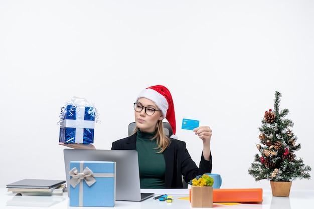 Femme d'affaires positive avec chapeau de père noël et portant des lunettes assis à une table tenant un cadeau de noël et une carte bancaire sur fond blanc