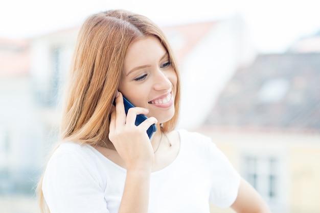 Femme d'affaires positive, parler au téléphone à l'extérieur