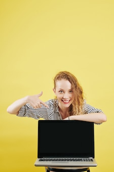 Femme d'affaires positive pointant sur l'écran de l'ordinateur portable