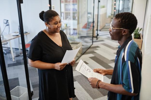 Femme d'affaires positive avec un rapport en main posant des questions à son collègue qu'elle a rencontré au bureau c...