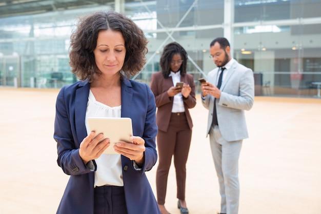 Femme d'affaires positive en regardant le contenu sur une tablette