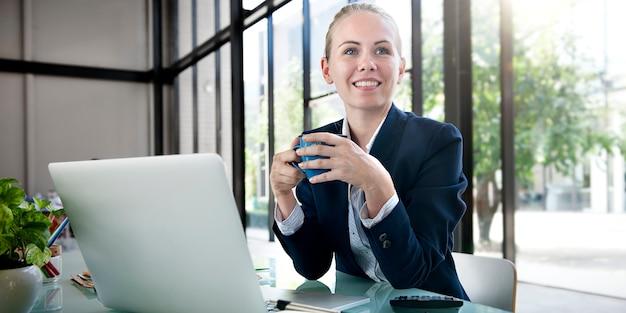 Femme d'affaires prenant un café alors qu'il travaillait au bureau