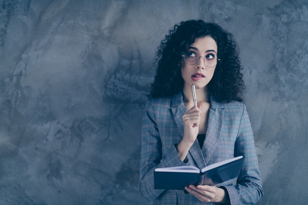 Femme d'affaires prenant des notes pense isolé sur mur gris