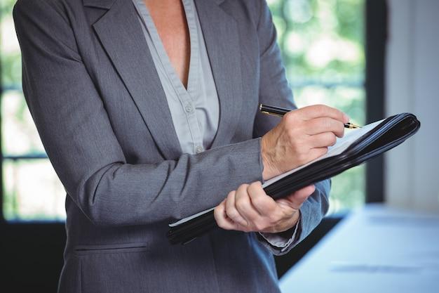 Femme d'affaires prenant des notes