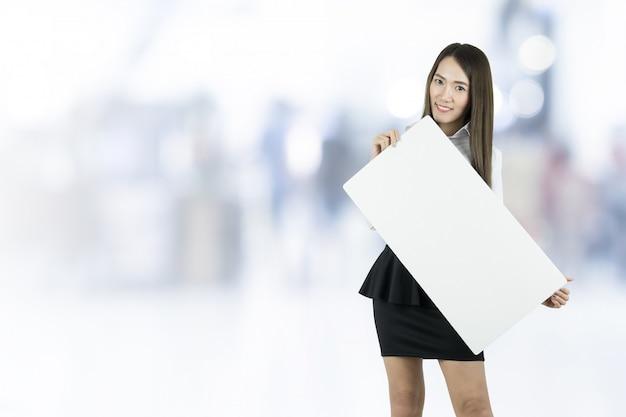 Femme d'affaires prenant tableau blanc vierge sur fond flou.