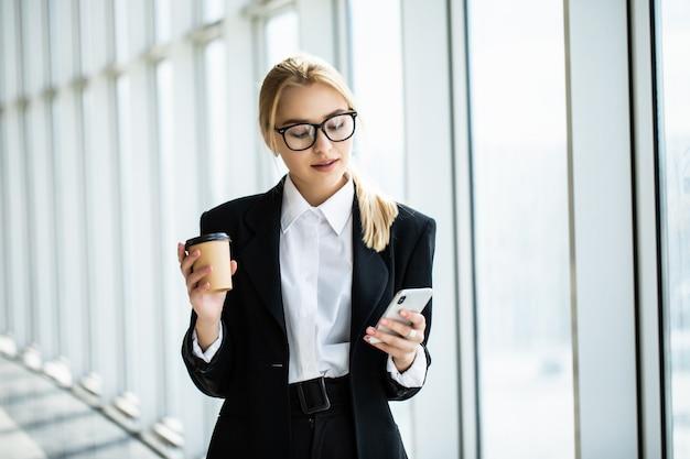 Femme affaires, prendre, café, pause, utilisation, smartphone, bureau