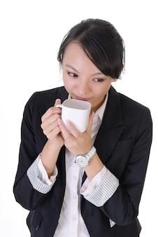 Femme d'affaires prendre une pause avec café, portrait agrandi sur fond blanc.