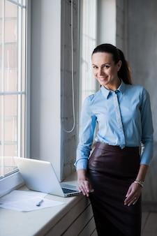 Femme d'affaires près des fenêtres lumineuses