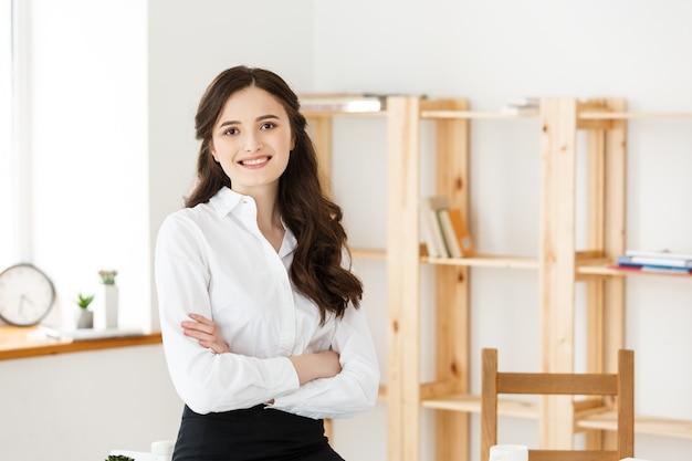 Femme d'affaires professionnelle mature souriante avec les bras croisés assis sur le bureau au bureau.
