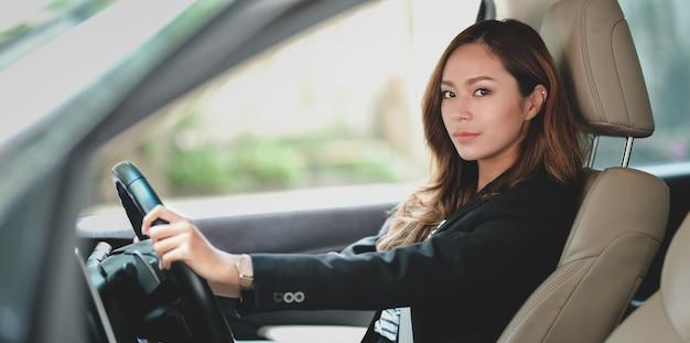 Femme d'affaires professionnelle à la recherche en conduisant la voiture