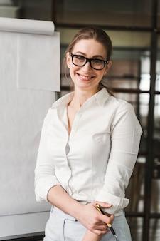 Femme d'affaires professionnelle smiley avec des lunettes faisant une présentation