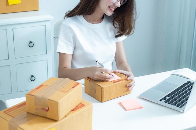 Femme d'affaires de propriétaire adolescent asiatique travaille à la maison pour les achats en ligne et la vente.
