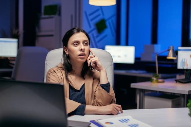 Femme d'affaires prospère ayant une conversation téléphonique le soir assise sur le lieu de travail. femme entrepreneur travaillant tard le soir dans une entreprise faisant des heures supplémentaires au cours d'un appel téléphonique.