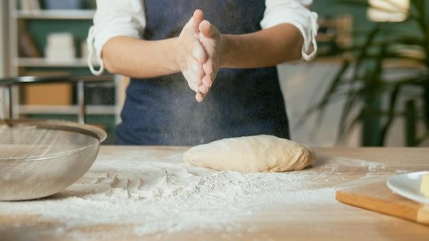Une femme d'affaires prospère est heureuse de pétrir la pâte sur une table en bois