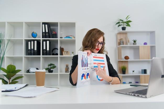 Femme d'affaires prospère expérimentée dans des vêtements et des lunettes élégants parlant avec son partenaire commercial par appel vidéo et montre un rapport avec des graphiques.