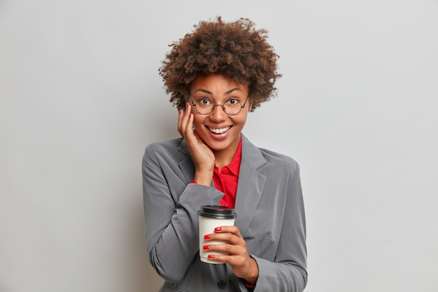 Une femme d'affaires prospère et joyeuse à la recherche agréable prend du café dans la cafétéria locale, se détend après la journée de travail, sourit positivement avec des dents blanches, boit une boisson aromatique