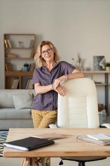 Femme d'affaires prospère mature debout près du lieu de travail tout en restant à la maison pour la période de quarantaine au cours de l'épidémie de covid19