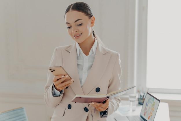 Femme d'affaires prospère regardant l'écran du smartphone avec le bloc-notes à la main, lisant les dernières nouvelles ou vérifiant les e-mails. employée souriante en costume formel beige travaillant dans un bureau moderne et léger