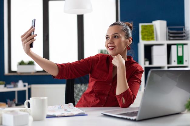 Femme d'affaires prospère s'amusant au travail en prenant des selfies