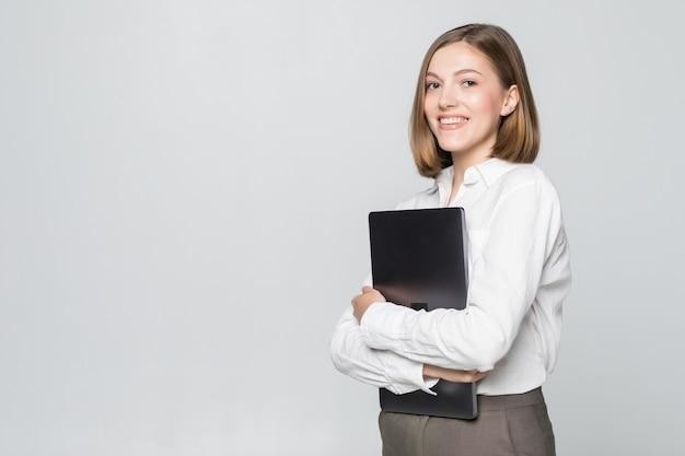 Femme d'affaires prospère tenant un ordinateur portable sur un mur blanc