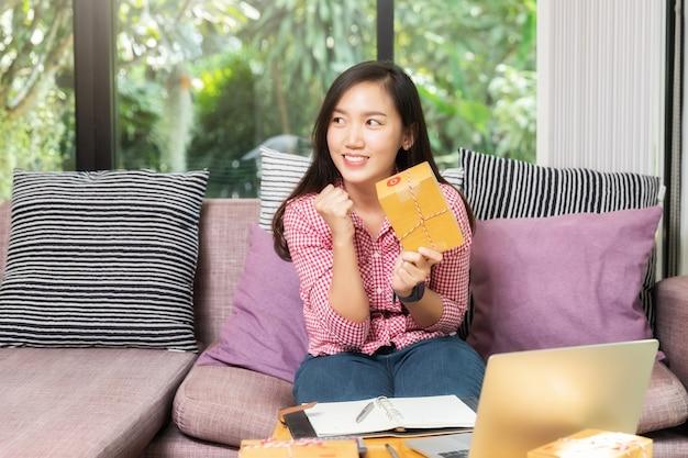 Femme d'affaires prospère avec vente en ligne et expédition de colis dans son bureau à domicile.