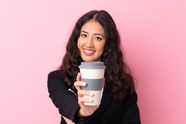 Femme d'affaires de race mixte tenant un café à emporter