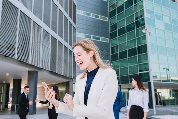 Femme d'affaires recevant de bonnes nouvelles sur smartphone