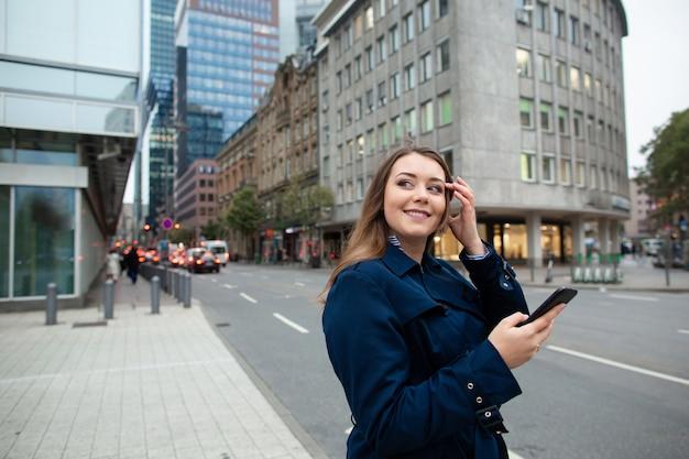 Femme d'affaires à la recherche d'un emplacement dans le téléphone, pour une réunion d'affaires. photo demi-longueur.