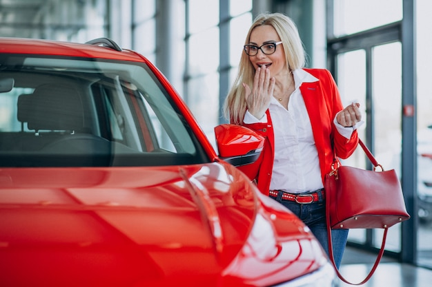 Femme d'affaires à la recherche d'un mobile auto dans une salle d'exposition de voitures