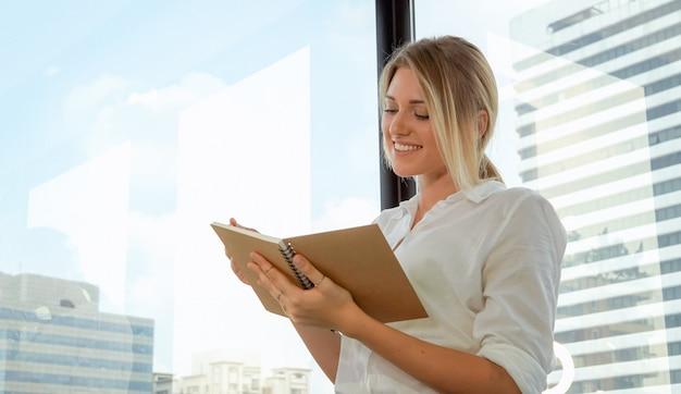 Femme d'affaires réfléchie au bureau écrit dans un cahier