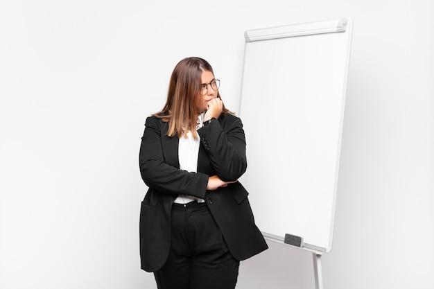 Femme d'affaires réfléchie devant un tableau blanc