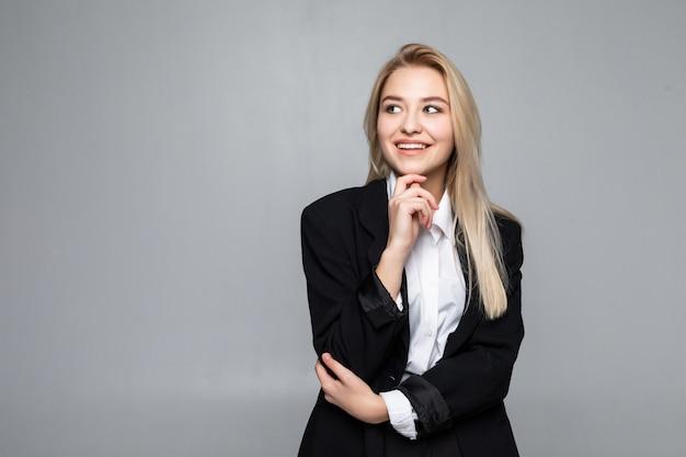 Femme d'affaires réfléchie avec un doigt sous le menton à la recherche d'isolement.