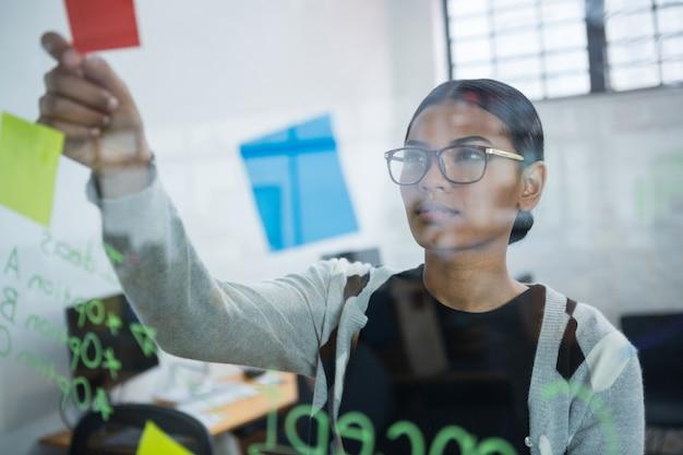 Femme d'affaires réfléchie, lecture de notes autocollantes sur verre