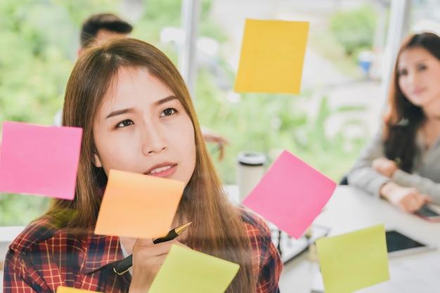 Femme affaires réfléchie, regarder, notes collantes, et, penser, sur, mur verre, dans, creat