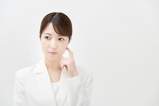 Une femme d'affaires avec un regard douteux et fond blanc