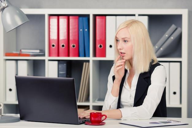 Femme d'affaires regardant un écran d'ordinateur au bureau