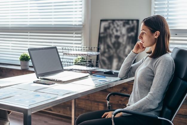 Femme d'affaires regardant un écran d'ordinateur portable tout en travaillant au bureau.