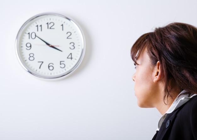 Femme d'affaires en regardant une horloge