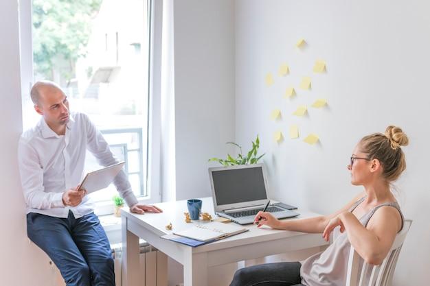 Femme affaires, regarder, elle, partenaire, tenue, tablette numérique graphique, dans bureau