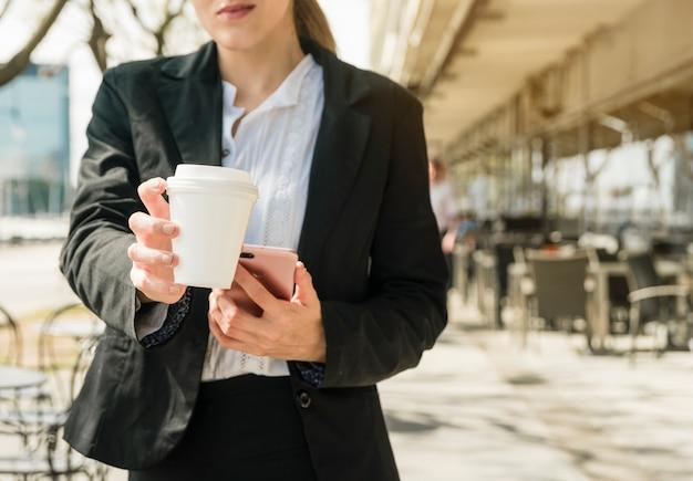Femme affaires, remise, tasse de café à emporter, debout, dans, les, restaurant extérieur