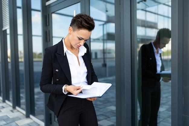 Femme d'affaires remplit des documents sur la façade d'un immeuble financier moderne