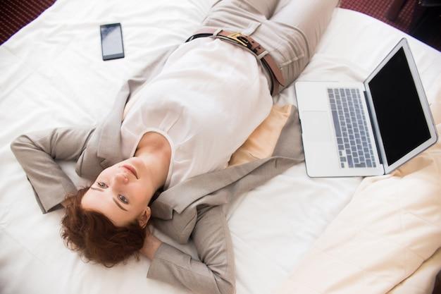 Femme affaires, reposer, hôtel, lit