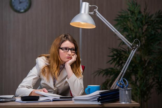 Femme d'affaires restant au bureau pendant de longues heures